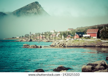 Red and yellow wooden fishing cabins in Norway - stock photo