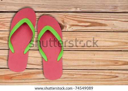 red ang green flip flop sandals on wood background - stock photo