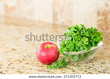 Red apple and a bowl of fresh green kale in a glass bowl on a granite counter top. Copy space. - stock photo