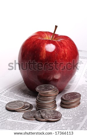 Red apple and coins isolated on a white background - stock photo