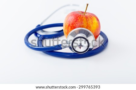 Red Apple and stethoscope on white background - stock photo