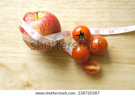 red apple and tomatoes wrapping with tape measure (diet concept) - stock photo