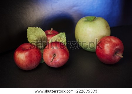 red apple contrast green foliage leaf on a dark background - stock photo