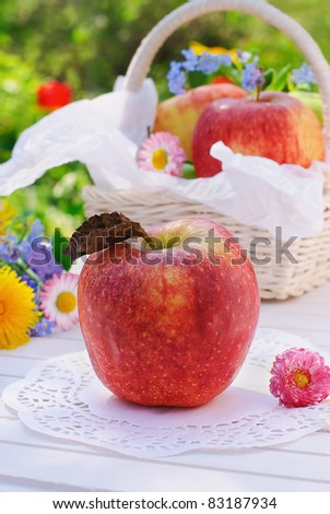 Red apple, flowers and basket on white garden table - stock photo