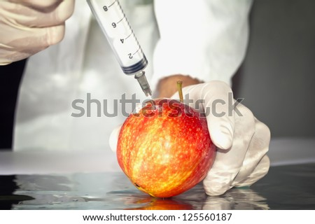 Red apple in genetic engineering laboratory, gmo food concept. - stock photo