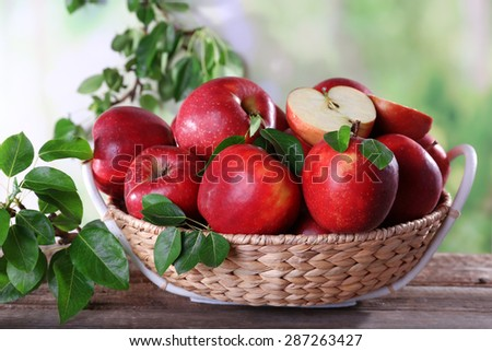 Red apple in wicker basket on wooden table, on blurred background - stock photo