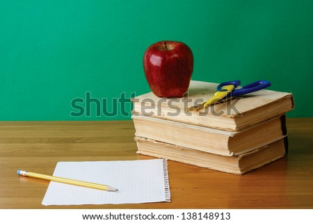 Red apple on a pile of books, paper and pencil on the desk - stock photo