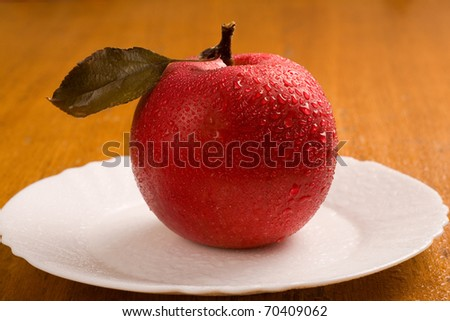 Red apple on white plate with green blade. - stock photo