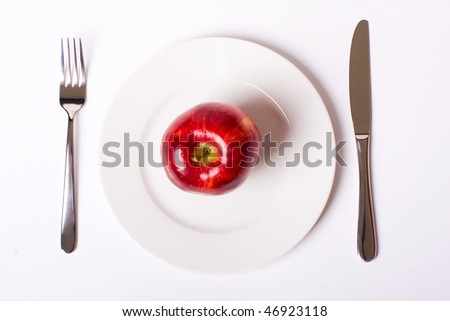 Red apple on white plate with knife and fork, with soft shadow - stock photo