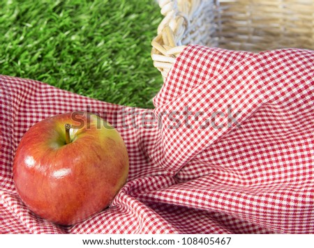 Red apple sitting on a checkered tablecloth in next to a wicker basket with grass in background - stock photo