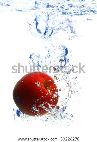 red apple under water with a trail of transparent bubbles. - stock photo