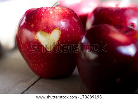 Red apple with a heart sign on the wooden table - stock photo