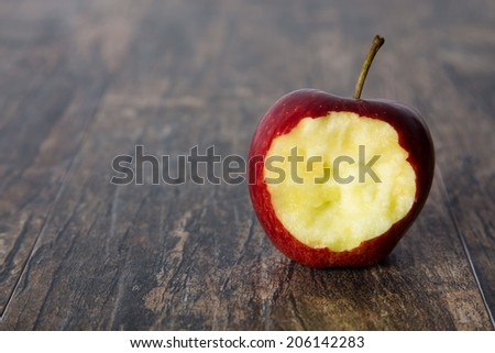 Red apple with a hole bitten into it on a brown wooden surface - stock photo