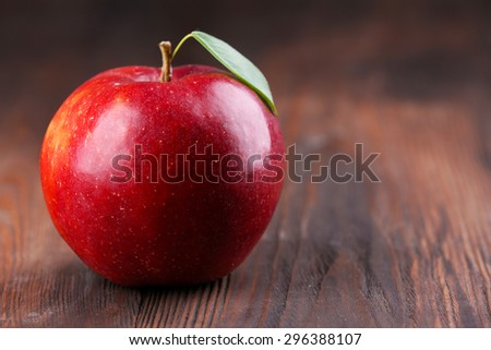 Red apple with leaf on wooden table, closeup - stock photo