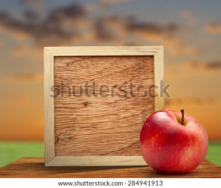 Red apple with wooden frame on nature background - stock photo