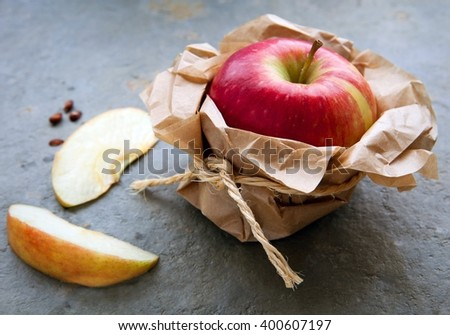 Red apple wrapped in brown paper on natural slate - stock photo