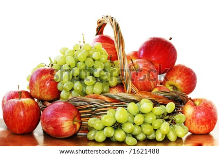 Red apples and grapes in a basket on a white background - stock photo