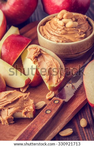 Red apples and peanut butter for snack, selective focus. - stock photo