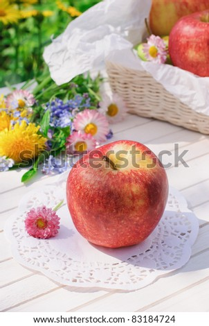Red apples, flowers and basket on white garden table in sunny summer day - stock photo