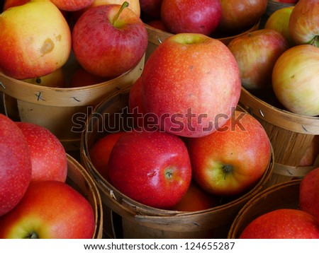 Red Apples sitting in a wooden basket at a farm market after being picked - stock photo