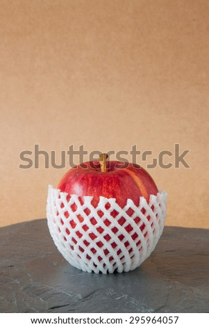 red apples with protective packaging on stone floor - stock photo