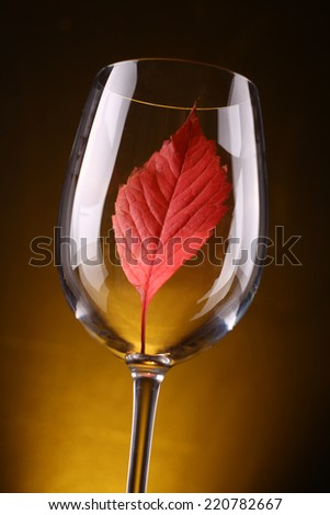Red autumn leaf in a tall wine glass over a warm dark background - stock photo