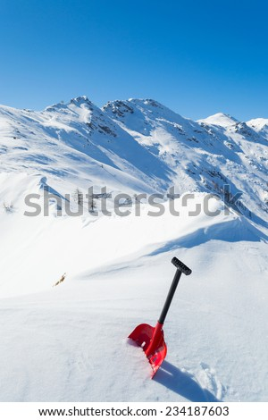 Red avalanche shovel in powder fresh snow. Scenic snowcapped high mountain background. Winter season in the italian Alps. - stock photo