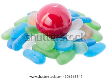 Red ball and glass stones on a white background. - stock photo