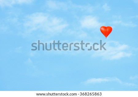 Red  balloon in the shape of heart in the blue haze sky. Soft tones pastel processing. Love concept background. Love and St Valentines day conception  with empty space for text - stock photo