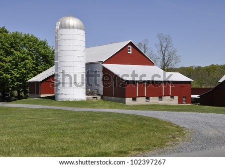 Red barn and a silo by a gravel road in eastern Pennsylvania.  There is a bright blue sky overhead and a green lawn. - stock photo