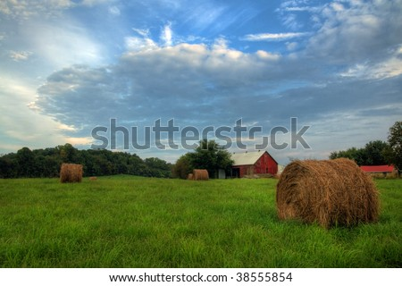 Red barn and hay bales in a field. - stock photo