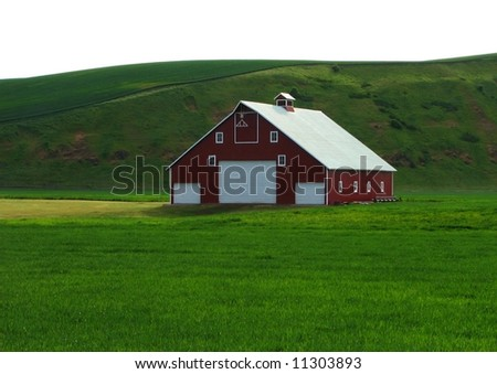 Red Barn Nestled in Green Hills - stock photo