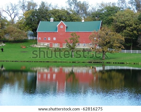 red barn reflected in water - stock photo