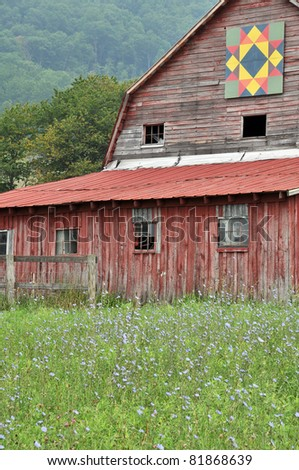 Red Barn with Quilt Block and Blue Chicory Foreground Vertical With Copy Space - stock photo