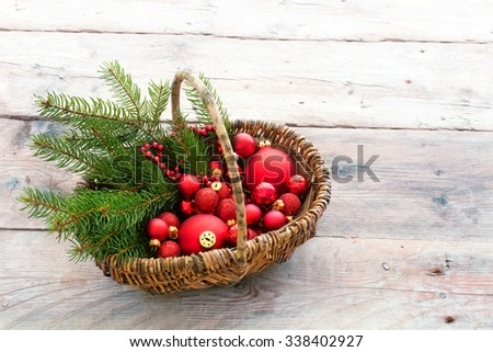 Red baubles to decorate the Christmas tree in a basket on rustic wooden floorboards, copy space - stock photo