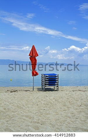 red beach umbrella and blue sunbeds at the deserted beach, Morning sea beach with sunbeds and red umbrella,red beach umbrella and blue sunbeds on a sandy beach, - stock photo