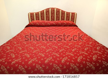 Red bed in a hotel room - stock photo