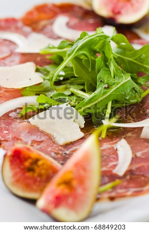 Red beef carpaccio in a white plate with salad, fig fruit, parmesan cheese and olive oil. Macro photography with shallow depth of field. - stock photo