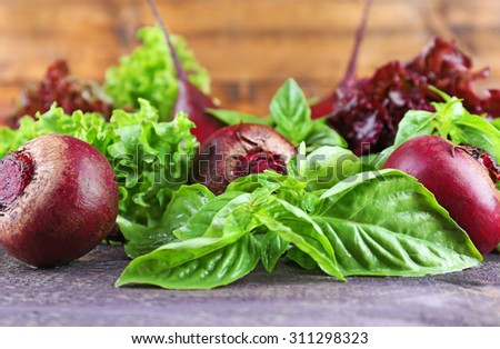 Red beets with greens on wooden table close up - stock photo