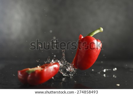 Red bell pepper dropped on wet limestone splashing water  - stock photo