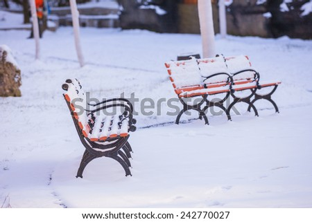 Red bench with shadow in snow in the Swiss Alps. - stock photo