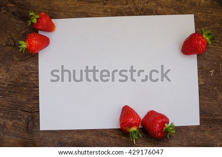 Red berry strawberry on rustic wooden background with sheet of paper. Background from freshly harvested strawberries with space for text. Strawberry background. Directly above. Top view. Copy space. - stock photo
