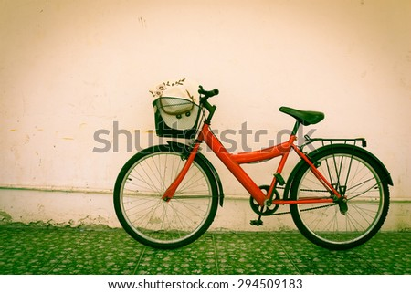 red bicycle on old dirty  house wall,vintage style. - stock photo