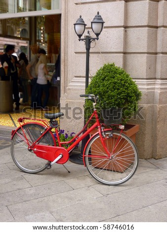 Red bicycle outside shop in Milan, Italy - stock photo