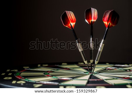 Red, black, and green dartboard on its side with three fiery metal tipped darts in the bulls eye. On black background. - stock photo