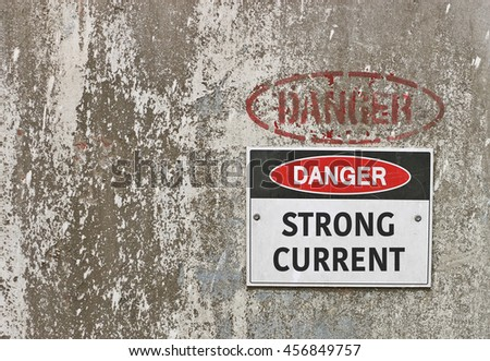 red, black and white Danger, Strong Current warning sign - stock photo