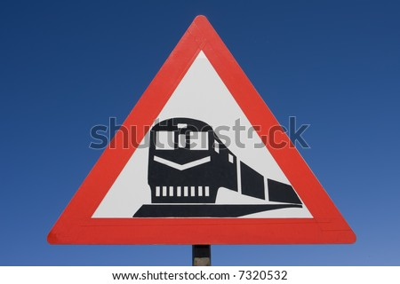 Red black and white rail road caution sign against a brilliant blue background - stock photo