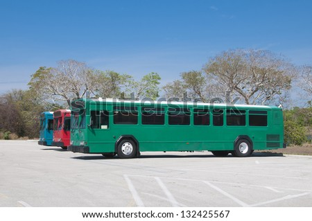 Red Blue and Green generic tour buses - stock photo