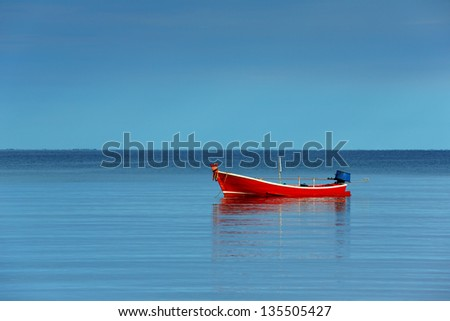 Red boat single row on sea with reflection in the water in the morning light - stock photo