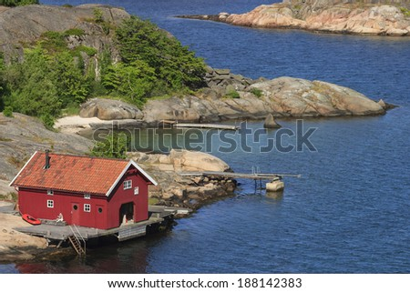 Red boathouse by the sea - stock photo